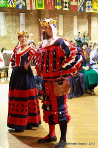 "Baronessa Maria Pagani and Baron Juan Xavier tribtue to the Patriots was a team effort.  It was a team effort. Pani Astrida Borowska made Maria's dresst. Lady Syele von Heidelberg made Juan's Wams and coif. Juan made the pants. Elvira Violante de Ballesteros made the red/white/blue cording. The coif slashes represent the team logo and the large ""X"" motif on the back of the Wams is both a play on my name, Xavier, and also makes him #10 on the team. Maria's gown has elements drawn from a Patriots cheerleader uniform."